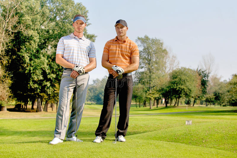 Portrait of young men standing with golf sticks on golf course royalty free stock images
