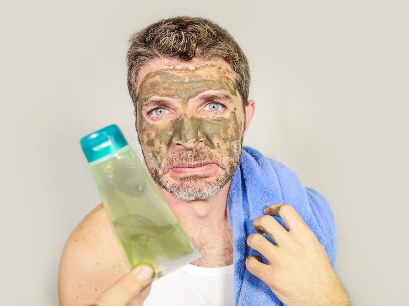 Portrait of young messy funny man in bathroom mirror with green face holding cream male beauty product applying facial mask feelin stock photography