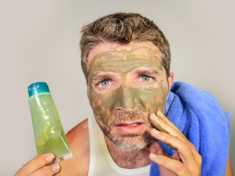 Portrait of young messy funny man in bathroom mirror with green face holding cream male beauty product applying facial mask feelin stock images