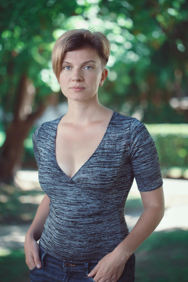 Portrait of young middle aged white caucasian girl woman with short hair stylish haircut in tshirt looking in camera stock photography