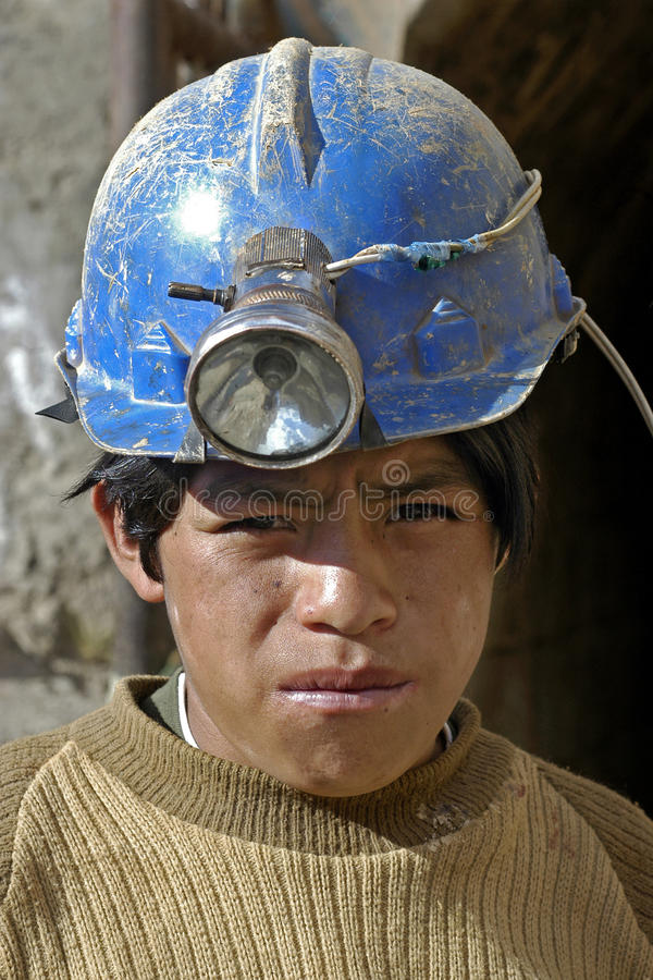Portrait of young miner, child labor in Bolivia. BOLIVIA, city Huanuni - Portrait of Indian boy and miner at the entrance to the mine shaft [Corporacion Minera stock images