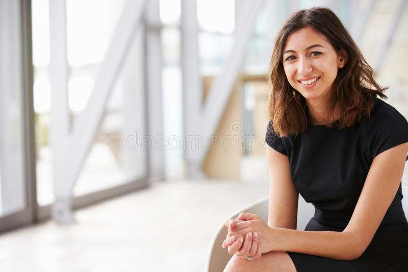 Portrait of young mixed race Asian businesswoman sitting royalty free stock photos