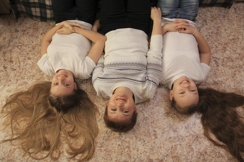 Portrait of young mom and her two teen daughters lying on the floor at home royalty free stock photography