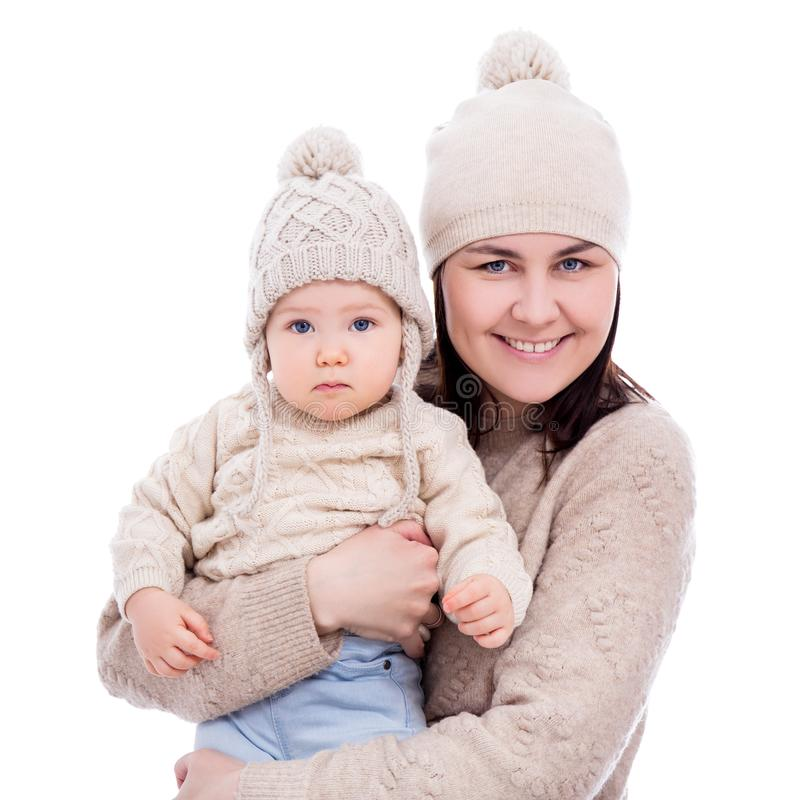 Portrait of young mother and cute baby girl in winter clothes isolated on white royalty free stock photography