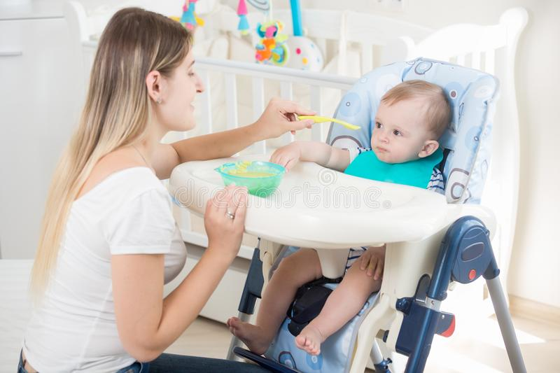 Portrait of young mother feeding her baby son sitting in highchair. Portrait of mother feeding her baby son sitting in highchair royalty free stock images