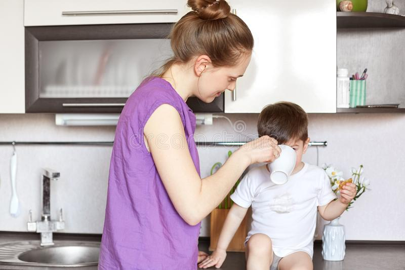 Portrait of young mother gives drink to her little son who sits on kitchen furniture, take care of small kid, being busy on matern royalty free stock photos