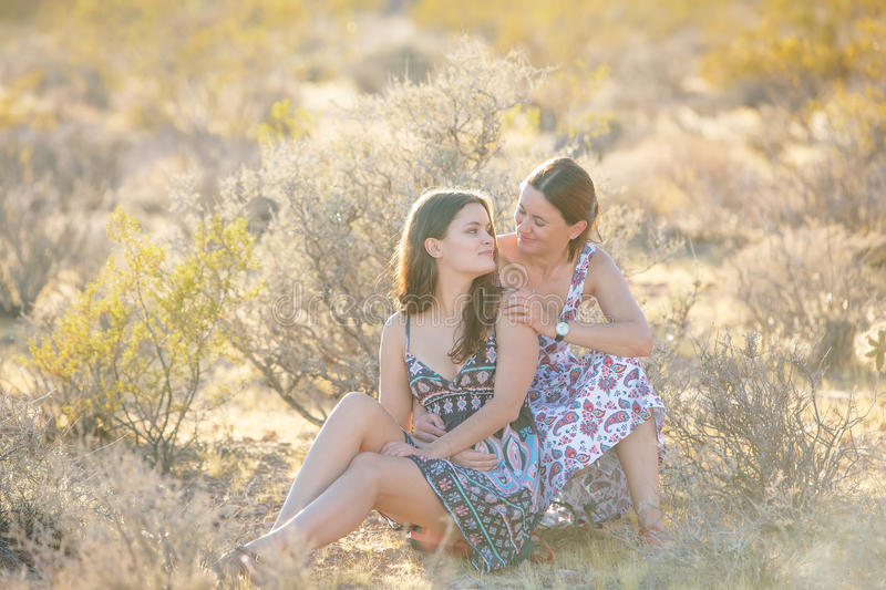 Portrait of a young mother and her daughter in desert royalty free stock image