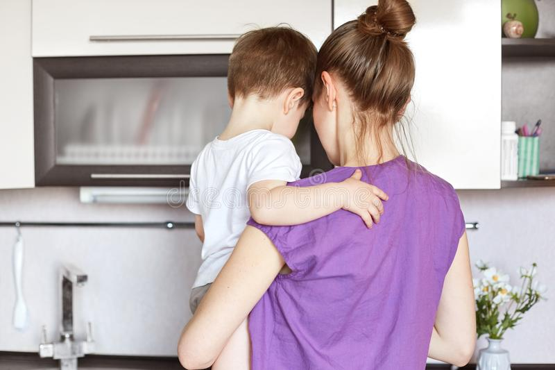 Portrait of young mother holds little son on hands, stand back together, work on kitchen, going to eat delicious dinner, takes car royalty free stock photo