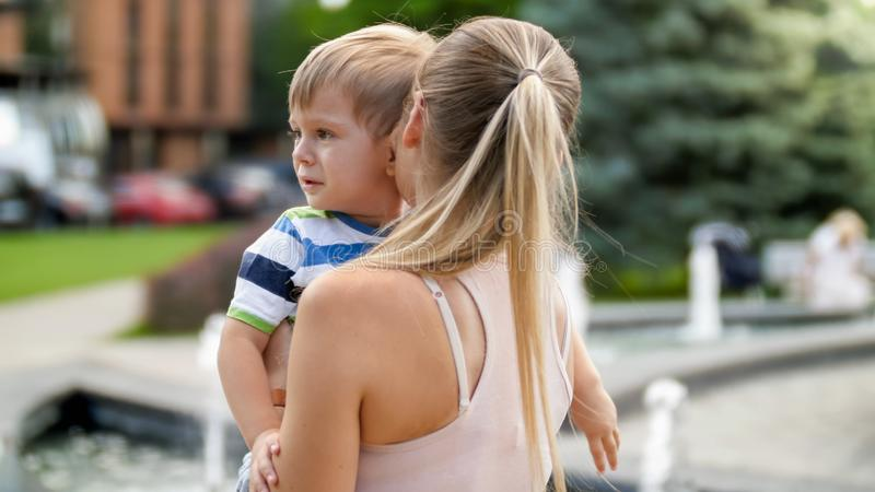 Closeup portrait of young mother hugging and caressing her crying little child boy in park stock image