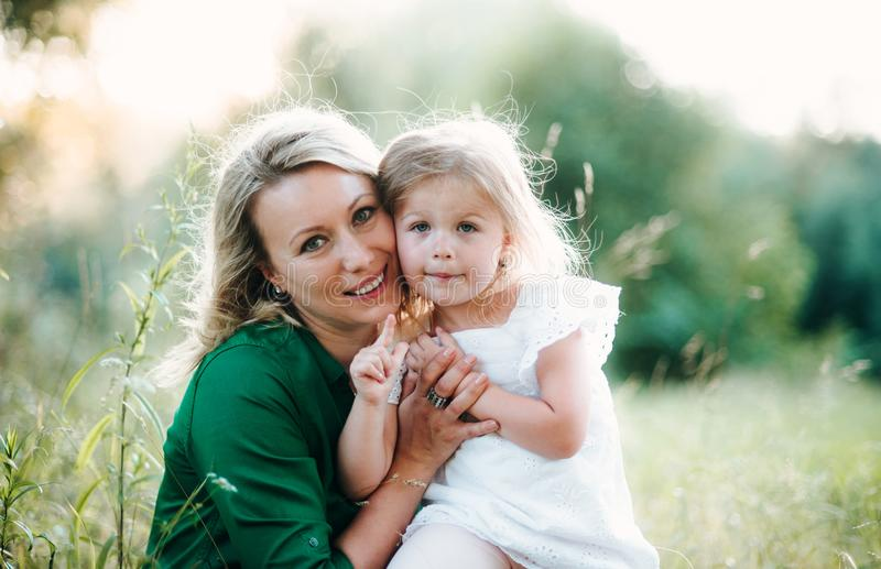 A portrait of young mother in nature with small daughter in summer. A front view stock photos