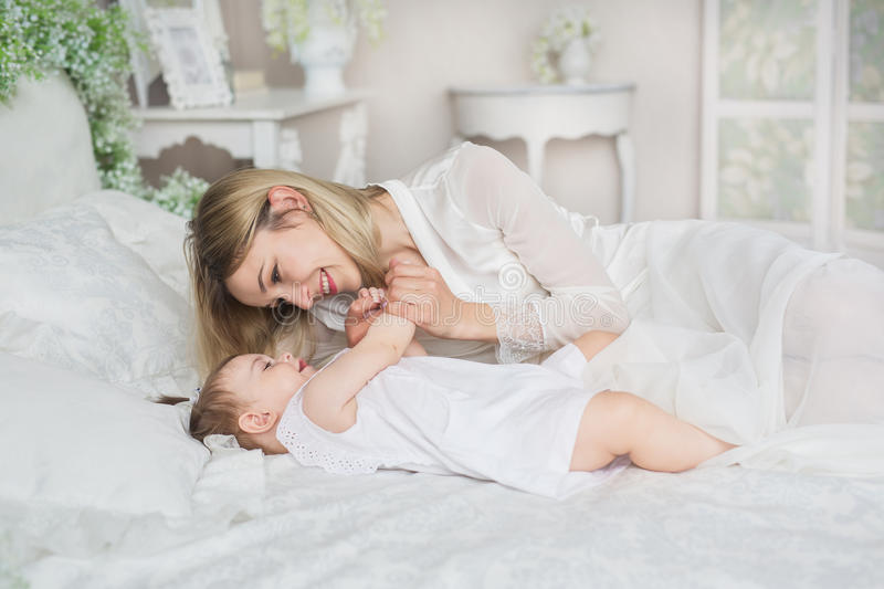 Portrait of young mother plays with her little baby on a bed stock image
