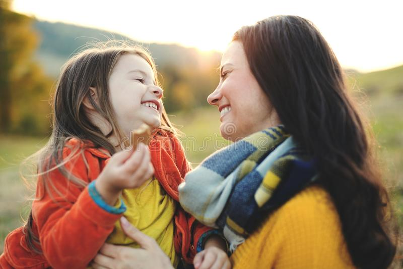 A portrait of young mother with a small daughter in autumn nature at sunset. royalty free stock images