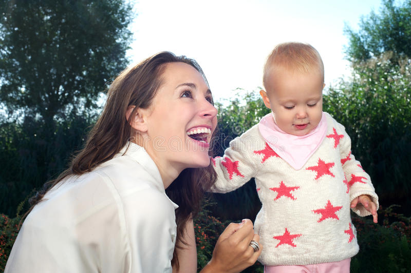 Download Portrait Of A Young Mother Smiling With Cute Baby Outdoors Stock Photo - Image: 33768940