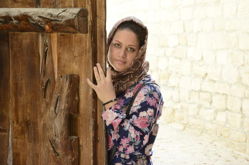 Portrait of a young muslim woman behind wooden door stock photography