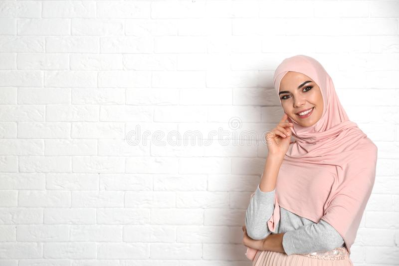 Portrait of young Muslim woman in hijab against wall. Space for text royalty free stock images