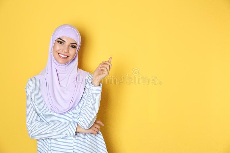Portrait of young Muslim woman in hijab against color background. stock photo
