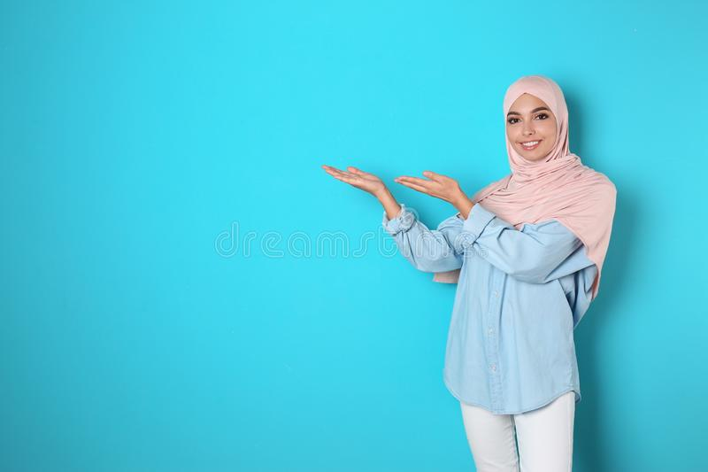 Portrait of young Muslim woman in hijab against color background. stock photography