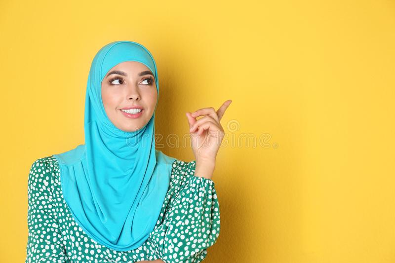 Portrait of young Muslim woman in hijab against color background. stock images