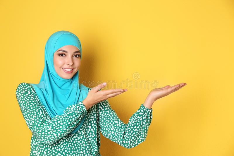 Portrait of young Muslim woman in hijab against color background. royalty free stock photo