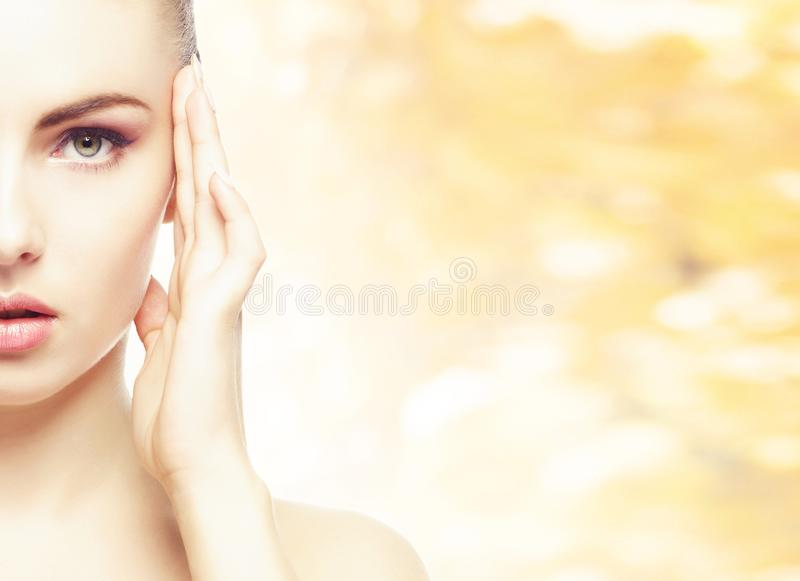 Portrait of young, natural and healthy woman over yellow autumn background. Healthcare, spa, makeup and face lifting. Portrait of young, natural and healthy stock images