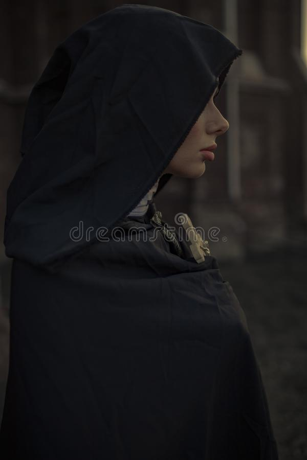 Portrait of young nun in black cassock and hooded cloak with cross. Portrait of young nun in black cassock and hooded cloak with cross in her hands. Side view stock photos
