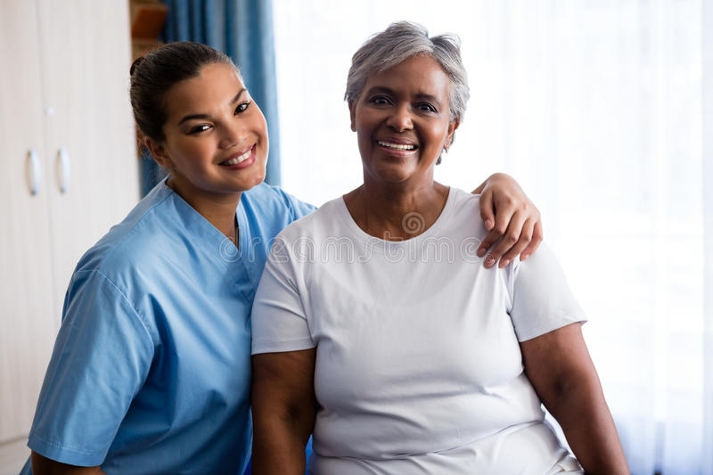 Portrait of young nurse with patient in nursing home royalty free stock photos