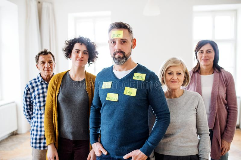 Young and old people standing with negative emotions adhesive notes during group therapy. stock photography