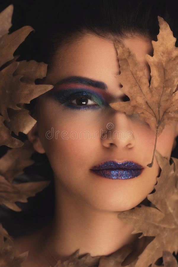 Portrait of young oman over autumn background. Healthcare, makeup and face lifting concept. royalty free stock photos