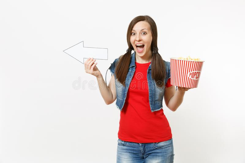 Portrait of young overjoyed woman in casual clothes watching movie film, holding bucket of popcorn, pointing white arrow. Aside on copyspace isolated on white royalty free stock image
