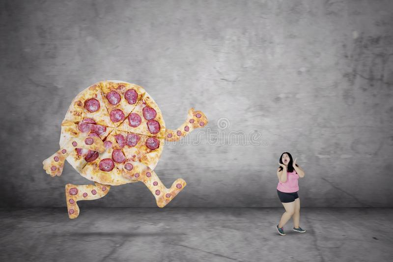 Overweight woman escaping from a pizza royalty free stock images