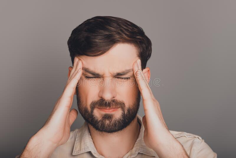 Portrait of young overworked businessman having migraine and suffering royalty free stock photography