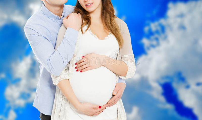 Portrait of young pair pending the kid isolated on blue background, Young attractive couple: pregnant mother and happy father, royalty free stock images
