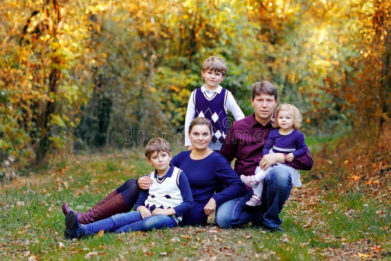 Portrait of young parents with three children. Mother, father, two kids brothers boys and little cute toddler sister royalty free stock image