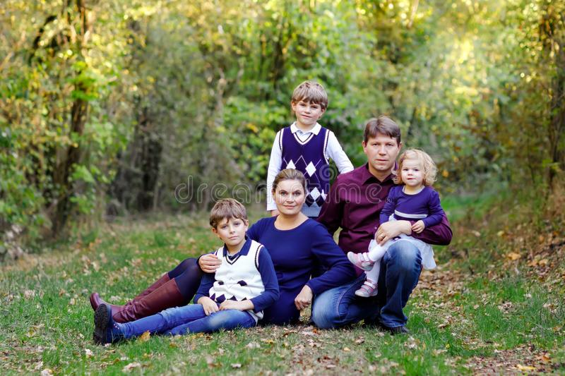 Portrait of young parents with three children. Mother, father, two kids brothers boys and little cute toddler sister. Girl having fun together in autumn forest royalty free stock photography