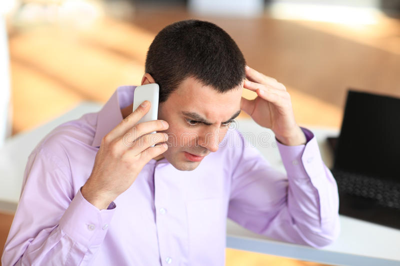 Portrait of young pensive businessman talking on cell phone in o stock image