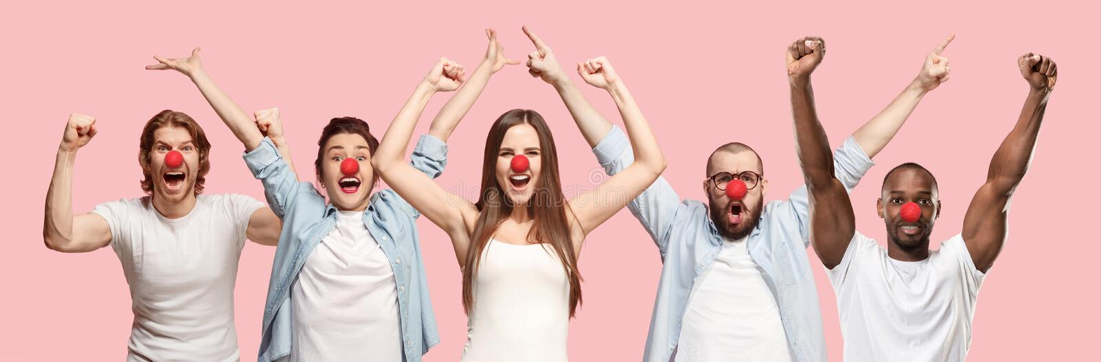 Portrait of young people celebrating red nose day on coral background stock image