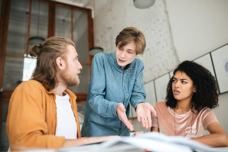 Young people emotionally discussing something in office. Two boys with blond hair and girl with dark curly hair working stock image