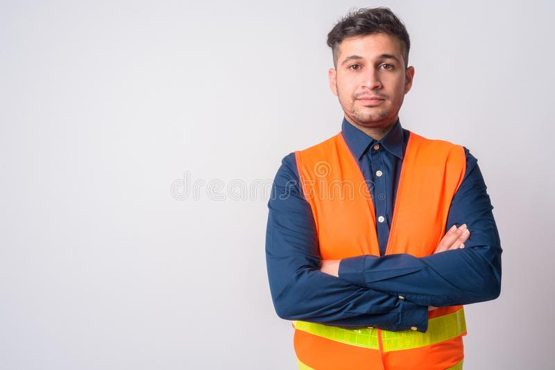 Portrait of young Persian man construction worker with arms crossed royalty free stock photo