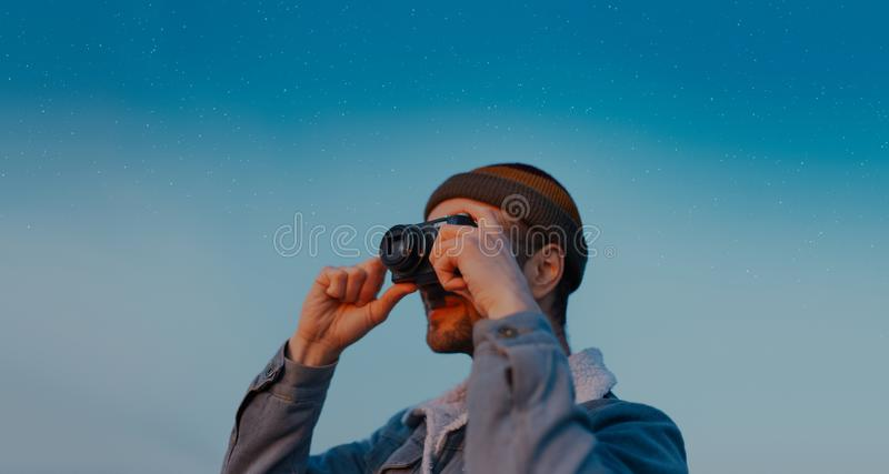 Portrait of young photographer taking photo with digital camera on background of blue starry sky. Modern man wearing beanie hat an stock image