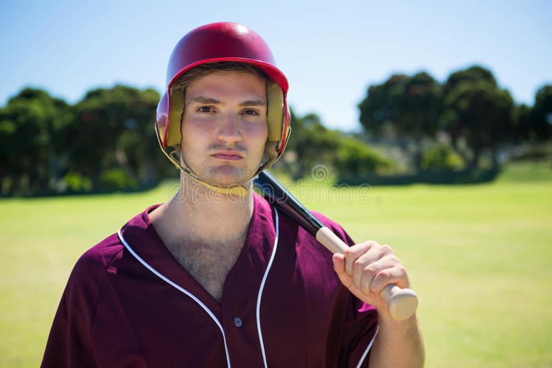 Portrait of young player holding baseball bat stock photos