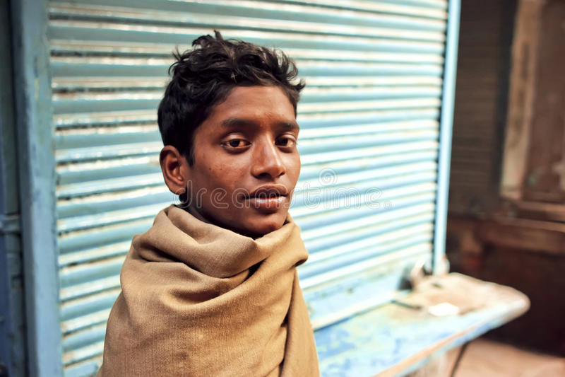 Portrait of young poor homeless man on abandoned street of indian city. VARANASI, INDIA - JAN 5: Portrait of young poor homeless man on abandoned street of stock photos