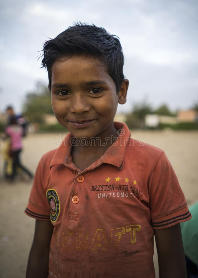 Portrait of young poor smiling boy in India. Jaipur, Rajasthan / India - 03 24 2019, Portrait of young boy, Poor kid in the slum area of the city royalty free stock images
