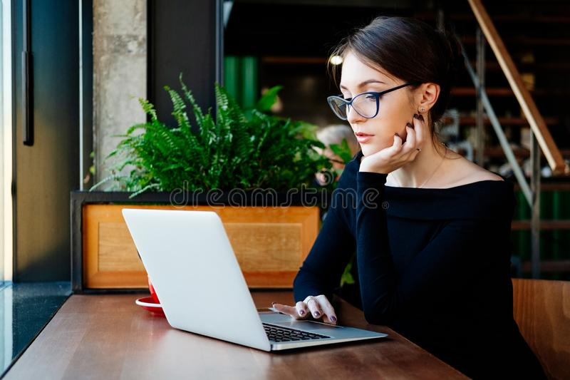 Portrait of young pretty business woman in glasses sitting on cafe and using laptop stock image