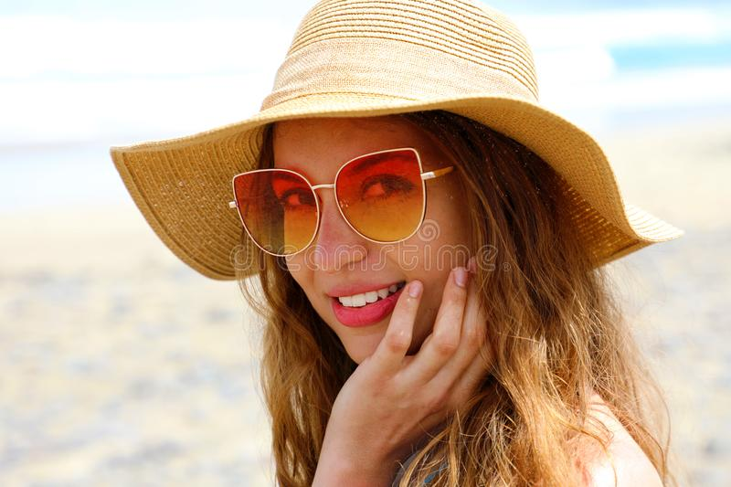 Portrait of young pretty fashion woman with straw hat and sunglasses on the beach. Vacation at sea, summer holidays royalty free stock photography