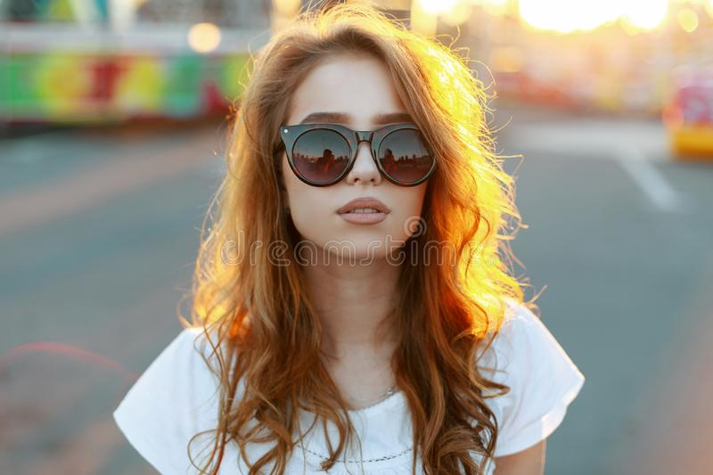Portrait of a young pretty hipster woman`s face in stylish sunglasses with red curly hair in a stylish T-shirt. On the background of bright orange summer sun royalty free stock photo
