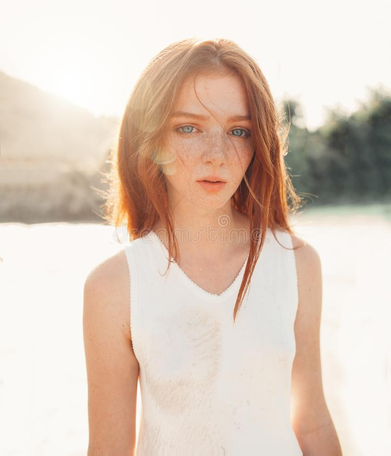 Portrait of the young pretty red-haired woman standing in the nature stock images