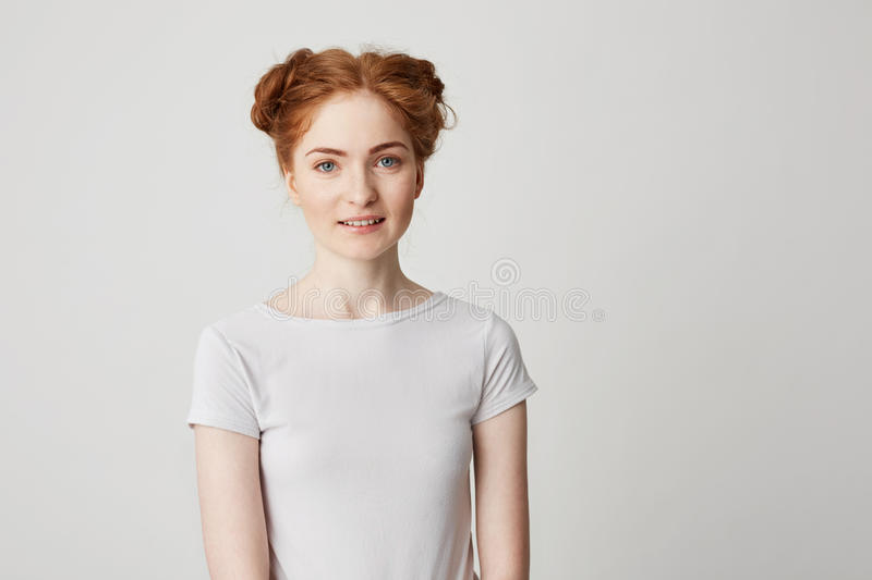 Portrait of young pretty redhead girl with buns looking at camera smiling over white background. stock image