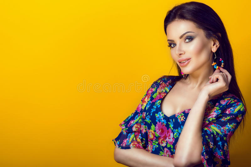 Portrait of young pretty smiling brunette in blue low-necked dress with bright floral print holding multi color stone earring royalty free stock images