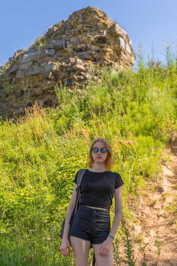 Portrait of young pretty tourist lady in sunglasses on the background of ancient architectural attractions ruins in sunny summer. Day. Travel concept stock images