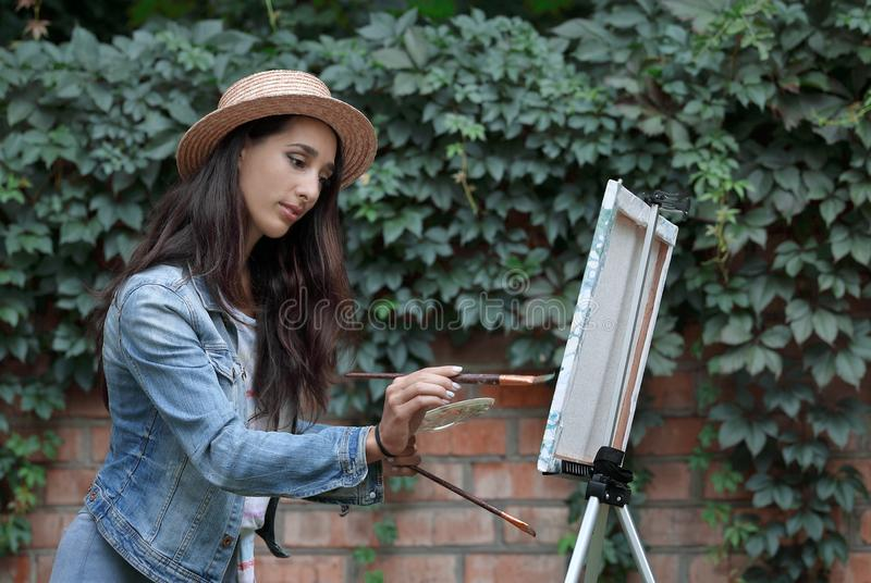 Portrait of young pretty woman in hat painting a picture using brushes and modern easel on nature in a summer park next to brick stock images